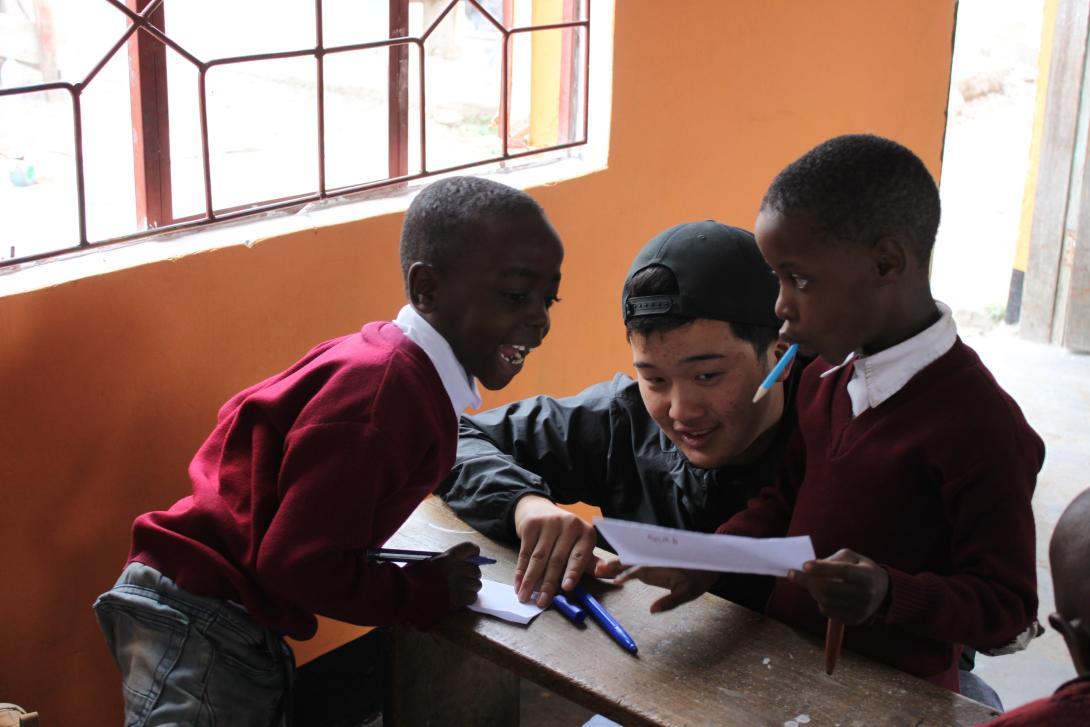 Un joven ayuda a dos niños con sus habilidades en inglés durante su voluntariado en el extranjero para jóvenes.